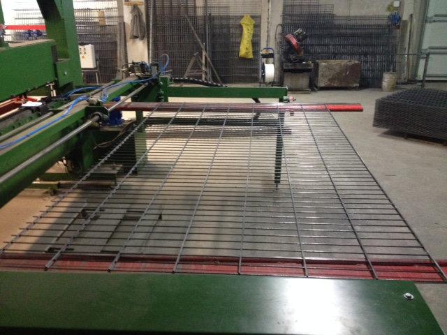 Herstellung von Doppelstabzaun: Ein fertiges Doppelstabzaunfeld kommt aus der Maschine raus.